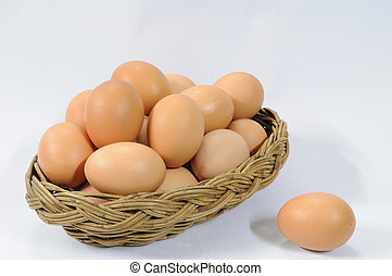 Many eggs in rattan basket on white table.