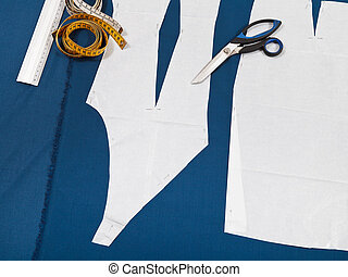 tailor tools and paper model of clothes on blue fabric for...
