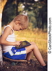 Boy Child playing with Tablet PC Outdoor with Summer nature...