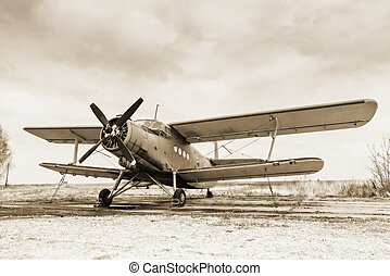 Old airplane on field in sepia tone