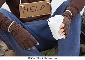Homeless waiting for alms - Homeless with paper cup waiting...