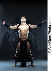Young muscular man posing as fallen angel in studio