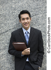 happy young Chinese business man in modern city - Chinese...
