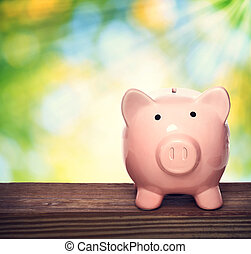 Piggy bank - Pink piggy bank over shiny leaves background