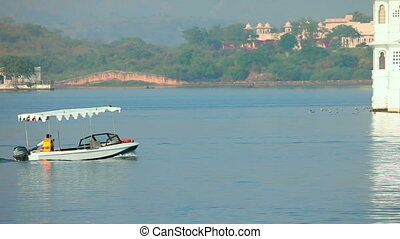 Lake in Udaipur - Boat passing allong the lake palace near...