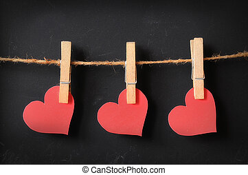three hearts hanging on blackboard background