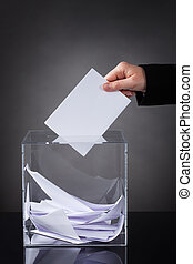 Hand Putting Ballot In Box - Close-up Of Hand Putting Ballot...
