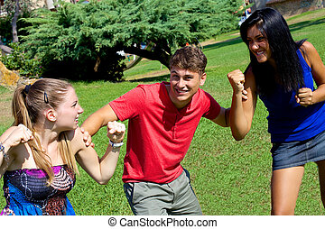 Young man holding two girls fighting for him - Handsome man...