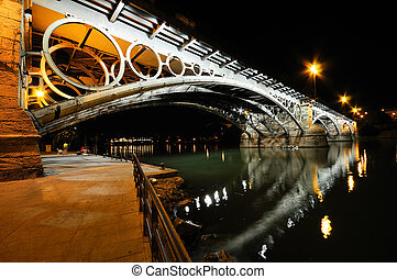 Isabel II bridge over Guadalquivir river at sunset with...
