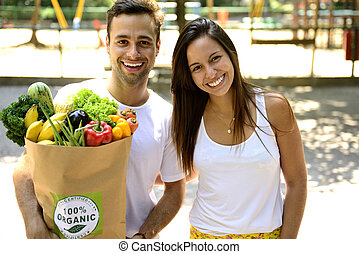 Happy couple carrying a bag of organic food. - Happy couple...