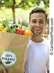 Happy man carrying bag of organic food. - Happy man carrying...