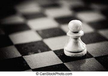 White chess pawn standing on chessboard - White chess pawn...