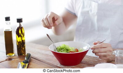 close of male hands mixing salad in a bowl - cooking and...