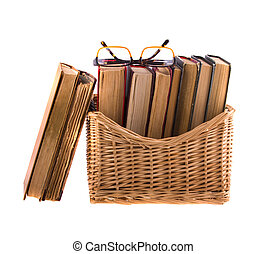 Stack of old antique books in a wicker basket and spectacles, isolated on white background.