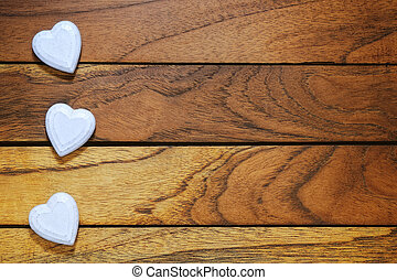 three white hearts misaligned with wood background