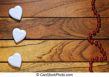 three white hearts misaligned and wood background with...