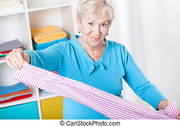 Elderly woman during folding laundry