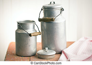 vintage milk cans on old wooden table