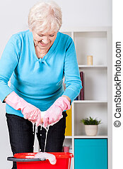 Elderly lady wringing cloth