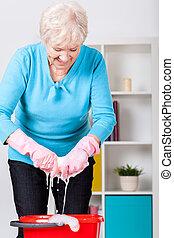Elderly lady wringing cloth