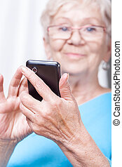 Senior lady using cellular phone application - Senior lady...