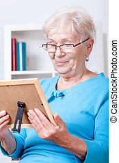 Elderly lady viewing family picture - Elderly lady wearing...