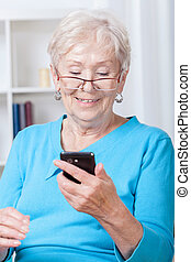 Elderly woman using mobile phone - Elderly woman during...