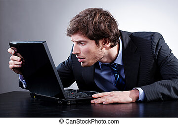 Man staring at screen of his laptop with anxiety