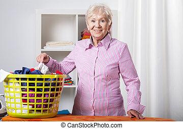 Senior lady during folding laundry - Senior lady wearing...