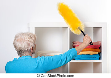 Elderly lady during dusting furniture at home