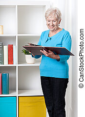 Senior lady viewing family album at home
