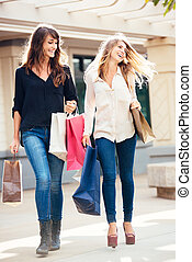 Two young women shopping at the mall - Two happy young women...