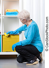 Elderly woman during dusting furniture at home