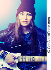 beautiful young woman sitting with guitar on blue background