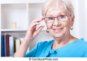 Grandmother wearing reading glasses - Smiling grandmother...