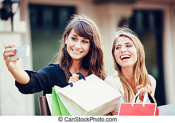 """Two young women shopping at the mall taking a """"selfie"""" or..."""