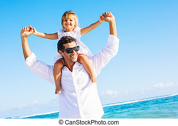 Father and daughter playing together at the beach - Healthy...