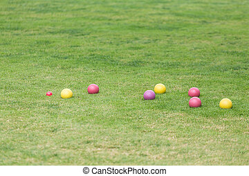 Colorful Bocce Balls in Green Lawn - Red, yellow and purple...