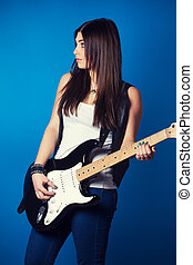 beautiful young woman with guitar on blue background