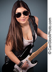 beautiful young woman wearing sunglasses with guitar on blue...