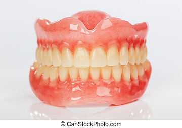 A set of dentures on a shiny white background