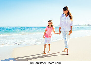 Happy mother and young daughter walking on the beach - Happy...