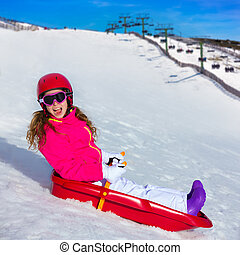 Kid girl playing sled in winter snow with helmet ang goggles