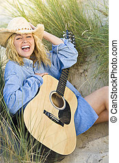 Happy Music In The Dunes - A beautiful blond young woman...
