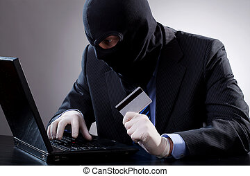 Hacker holding a credit card and using computer