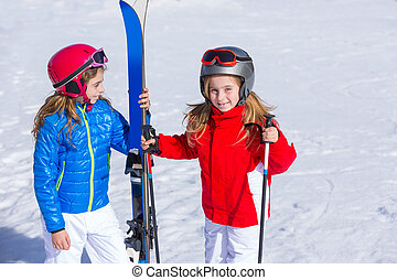 Kid girls sister in winter snow with ski equipment helmet...