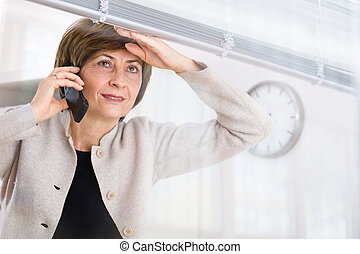 Looking away - Senior businesswoman looking through office...