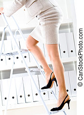 Archive - Businesswoman climbing on ladder to seek files on...