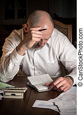 Man with checkbook - home finances stress