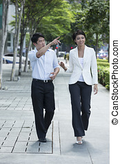 Two of Asian business colleagues walking in street - Two of...